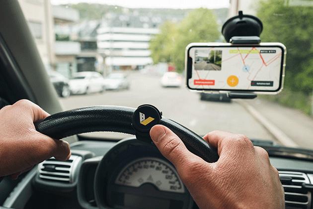 Smart-Button Hand am Lenkrad Smartphone in Windschutzscheibe